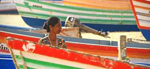 Frau zwischen Fischerbooten in Indien