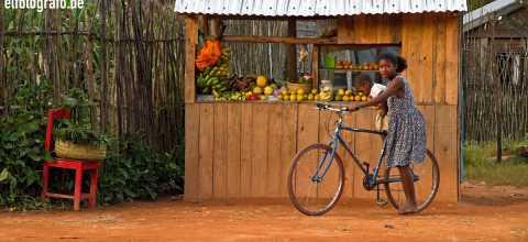 Junge Frau vor Obststand auf Madagaskar